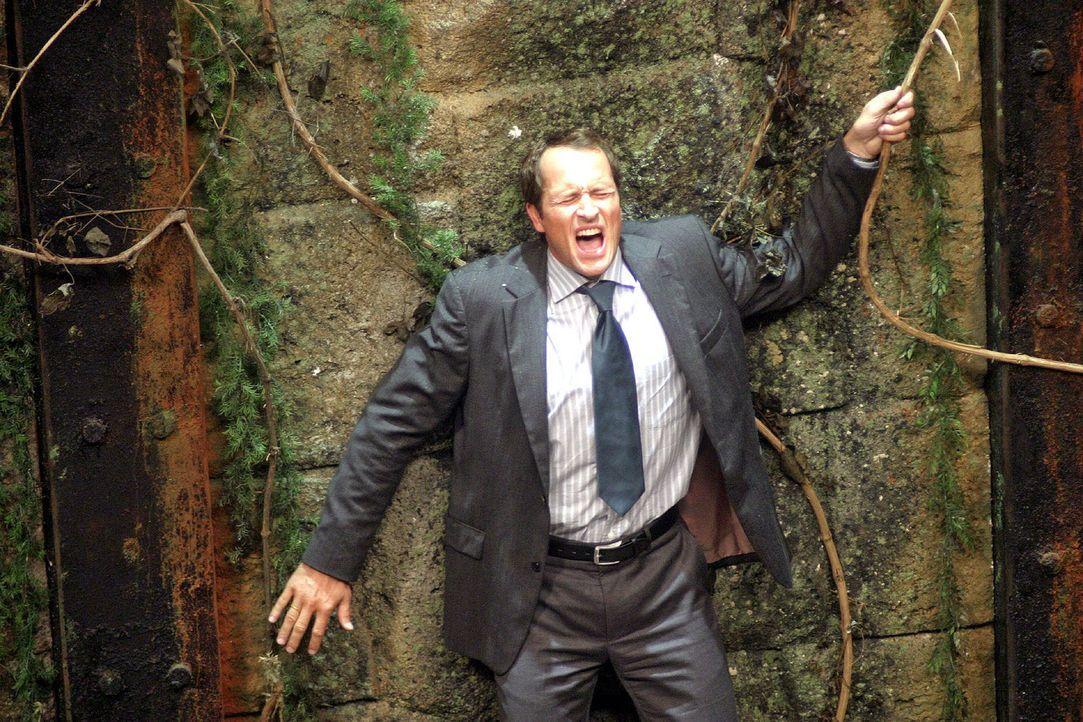 Mathias (Markus Knüfken) steht auf der Plattform, die sich langsam in die Felswand zurückzieht. 40 Meter weiter unten befindet sich ein mooriger B... - Bildquelle: Oktavian Cocolos Sat.1