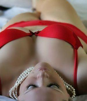 Frau liegt in sexy Pose auf dem Bett