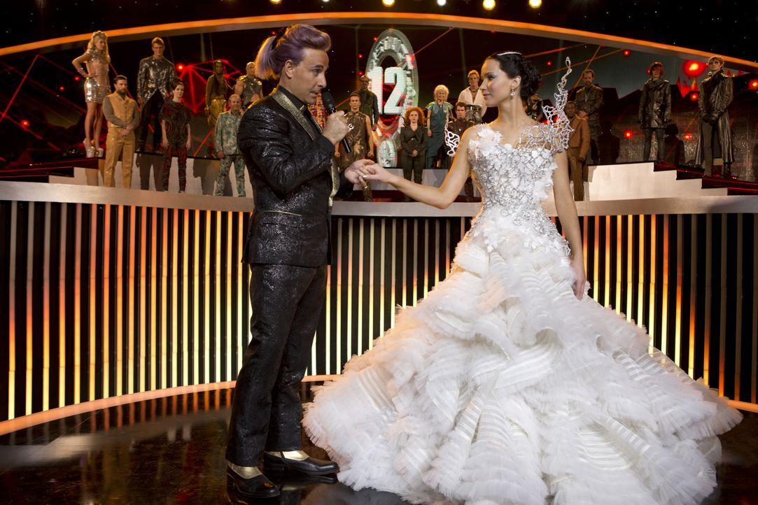 Moderator Caesar Flickerman (Stanley Tucci, l.) ahnt nicht, dass sich unter Katniss' (Jennifer Lawrence, r.) Brautkleid, das sie auf Snows Befehl hi... - Bildquelle: Studiocanal GmbH