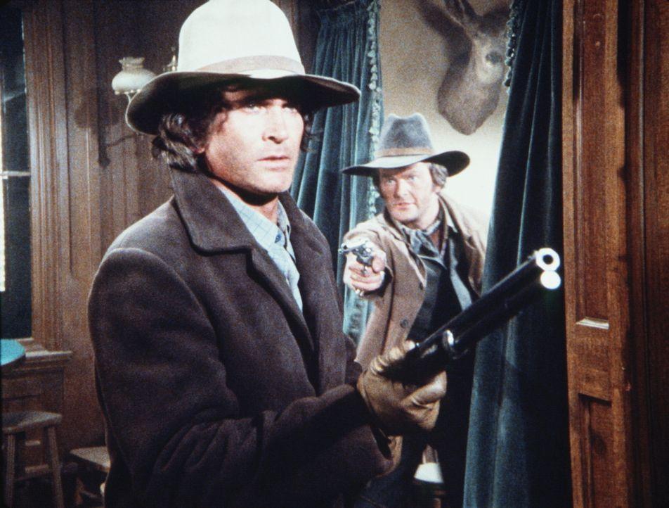 Coy (Chris Hendrie, r.) hat Charles Ingalls (Michael Landon, l.) überrascht und bedroht ihn von hinten. - Bildquelle: Worldvision