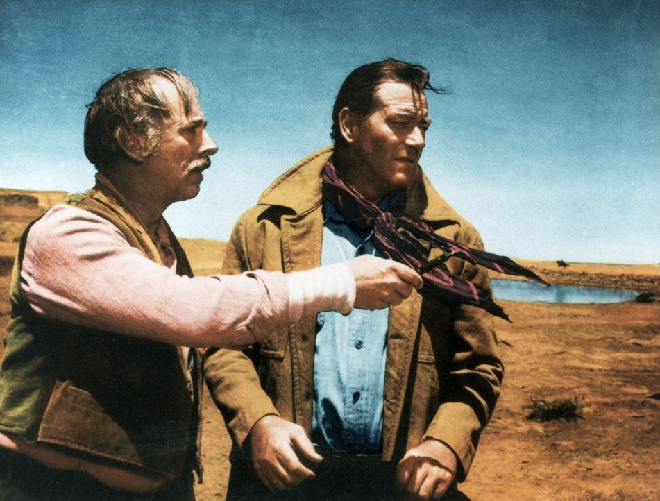 Lars Jorgensen (John Qualen, l.) zeigt Ethan Edwards (John Wayne, r.) in welche Richtung die Komantschen abgezogen sind ... - Bildquelle: Warner Bros.