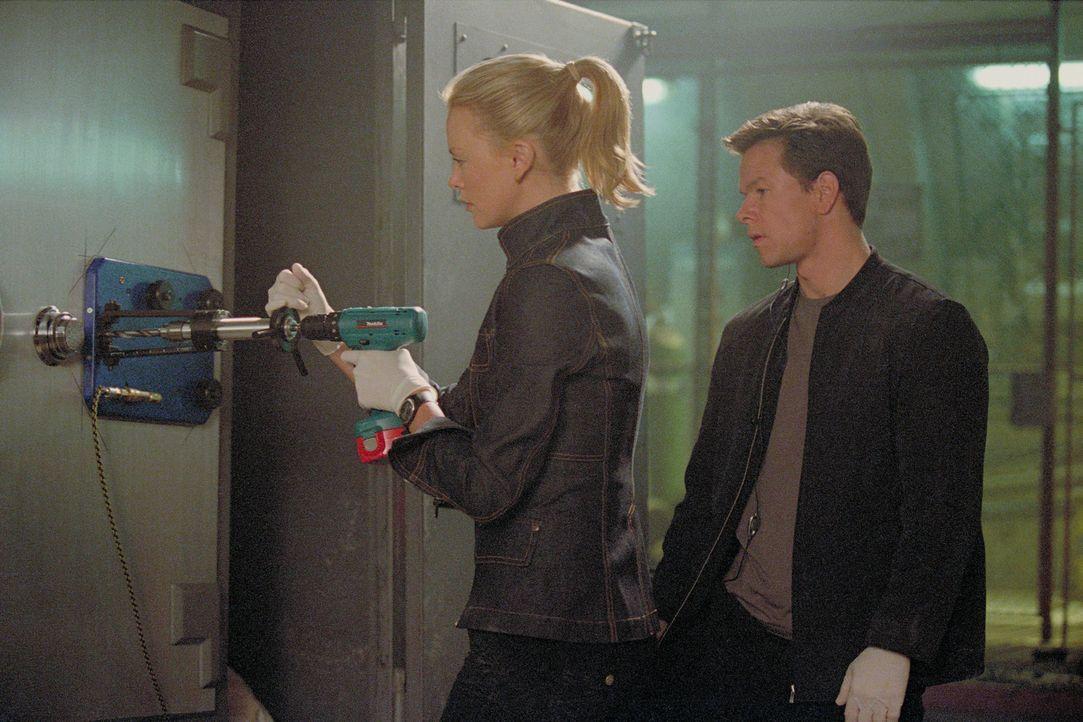 Gemeinsam mit Johns Tochter Stella (Charlize Theron, l.), die das Safeknackertalent ihres Vaters geerbt hat, tüftelt Charlie (Mark Wahlberg, r.) ein... - Bildquelle: TMG