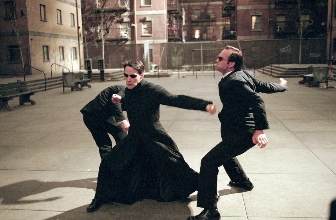 Agent Smith (Hugo Weaving, r.) erhält den Auftrag, Neo (Keanu Reeves, l.) zu liquidieren. Doch dann verweigert er dem System den Gehorsam ... - Bildquelle: Warner Bros.