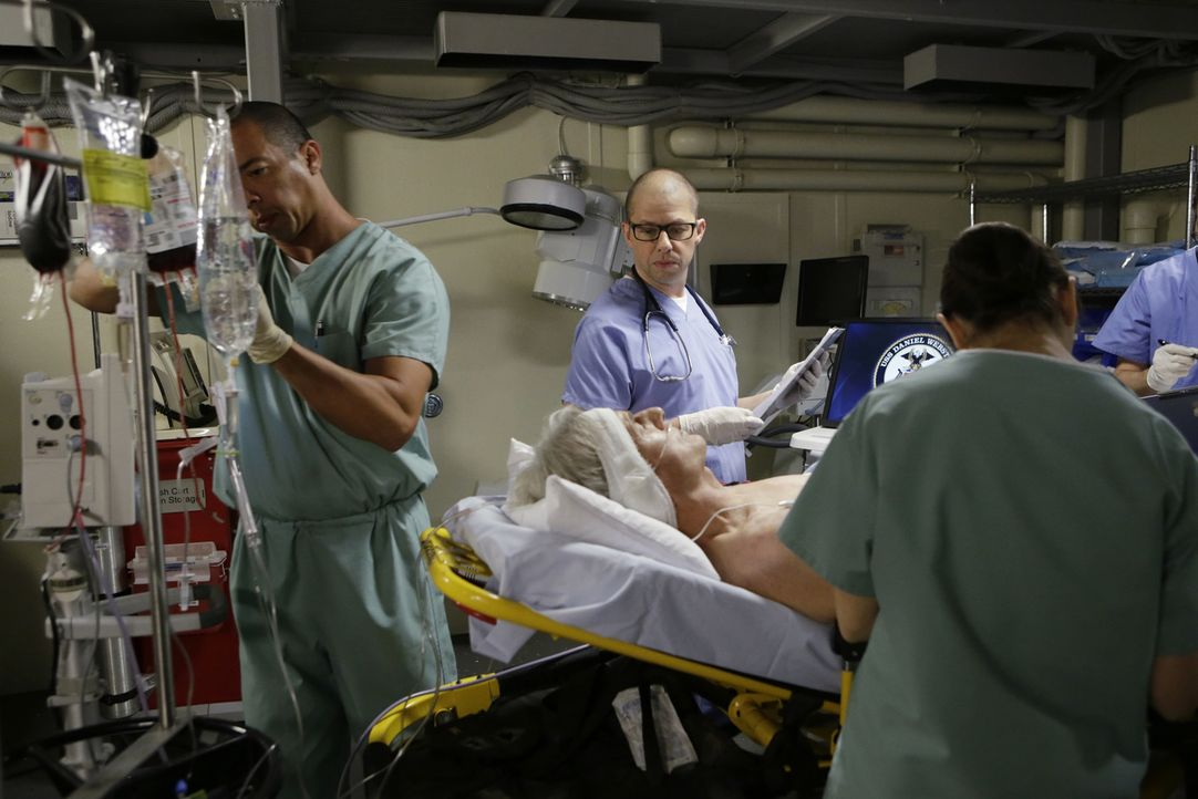 Nachdem Gibbs (Mark Harmon, liegend) von dem fehlgeleiteten Jungen Luke angeschossen wurde, versucht der engagierte Navy-Arzt Dr. Cyril Taft (Jon Cr... - Bildquelle: Sonja Flemming CBS Television