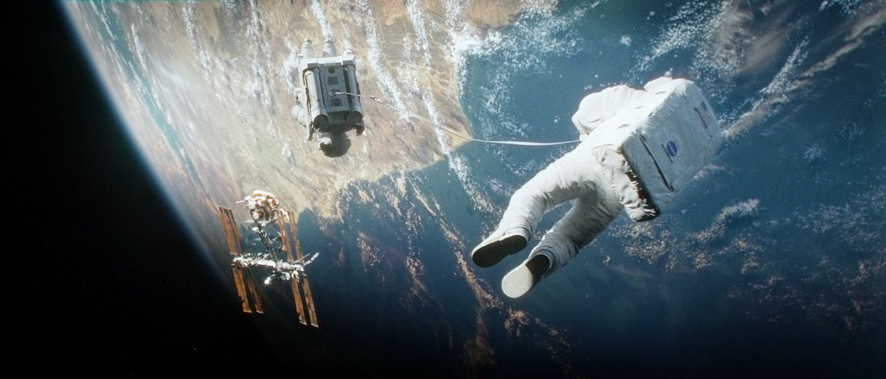 Als Trümmerteile ihr Shuttle zerstören, sind der altgediente Astronaut Matt Kowalski (George Clooney, r.) und die Biomedizinerin Dr. Ryan Stone (San... - Bildquelle: Warner Brothers