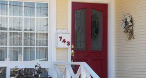 Rote Haustür mit Scheiben und goldenem Türgriff
