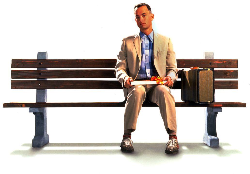Neben sich ein gepackter Koffer und auf seinen Knien eine Packung Pralinen. So sitzt Forrest Gump (Tom Hanks) geduldig an einer Bushaltestelle im S - Bildquelle: Paramount Pictures