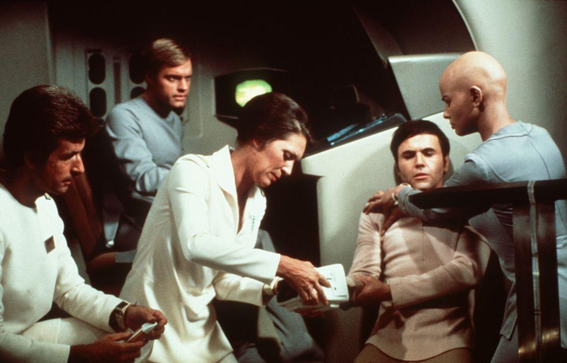 Cmdr. Chekov (Walter Koenig, 2.v.r.) wird beim Angriff verletzt. Dr. Christine Chapel (Majel Barrett, M.) und Ilia (Persis Khambatta, r.) kümmern s... - Bildquelle: Paramount Pictures