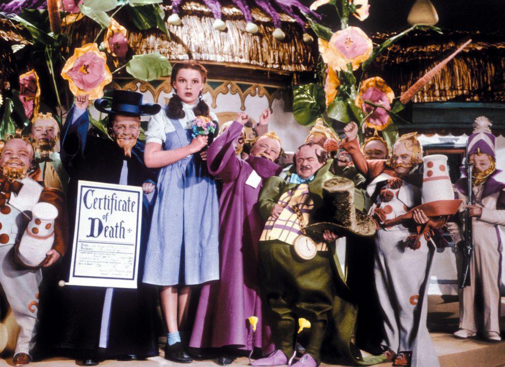 Dorothy (Judy Garland, M.) und die Zwerge des Landes Oz feiern ein Fest, weil die böse Hexe des Ostens tot ist ... - Bildquelle: Warner Bros.