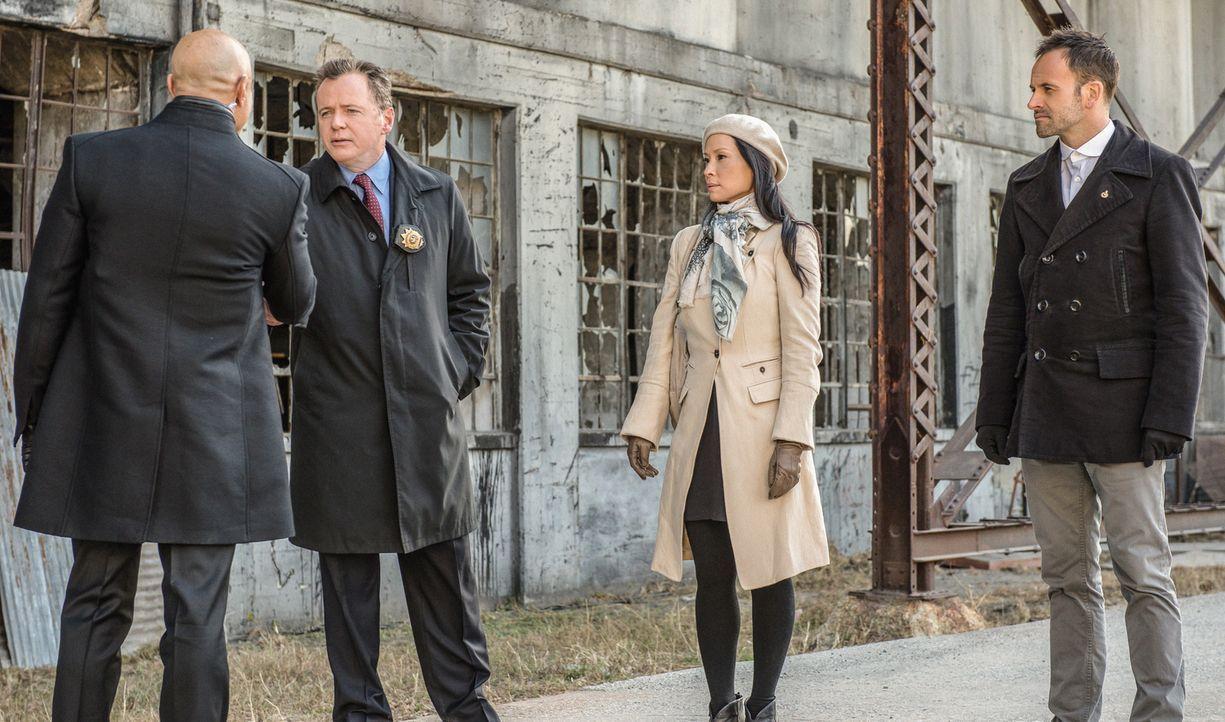 Capt. Gregson (Aidan Quinn, 2.v.l.), Dr. Watson (Lucy Liu, 2.v.r.) und Sherlock Holmes (Jonny Lee Miller, r.) lernen Moriartys Gefängniswärter Ramse... - Bildquelle: CBS Television