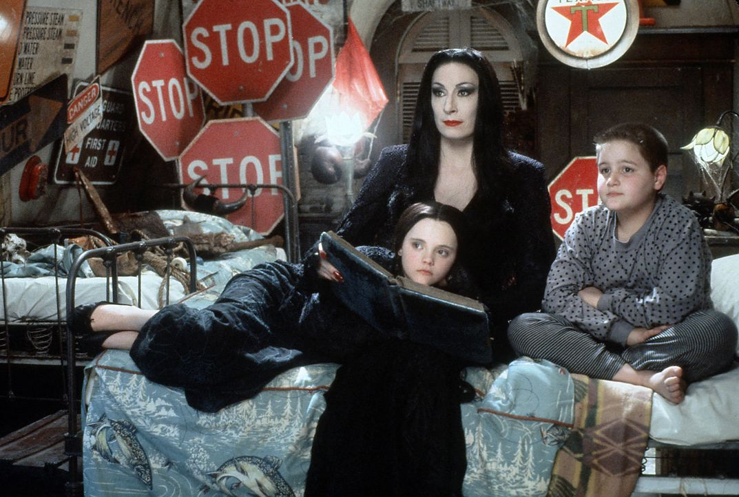 Morticia (Anjelica Huston, l.o.) ist Mutter des drallen Pugsley (Jimmy Workman, r.) und dessen sarkastischer Schwester Wednesday (Christina Ricci, l... - Bildquelle: Paramount Pictures Global