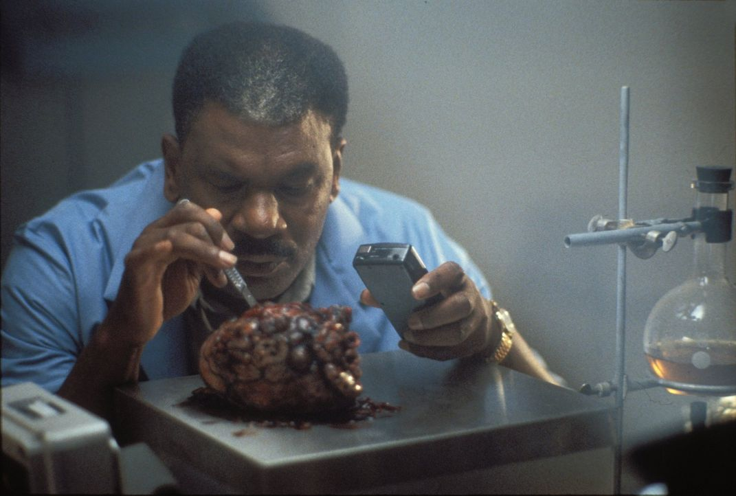 Der Coroner (Richard Grant) untersucht das Herz des vermeintlich getöteten Serienmörders - ohne zu ahnen, in welcher Gefahr er sich befindet ... - Bildquelle: Warner Bros.