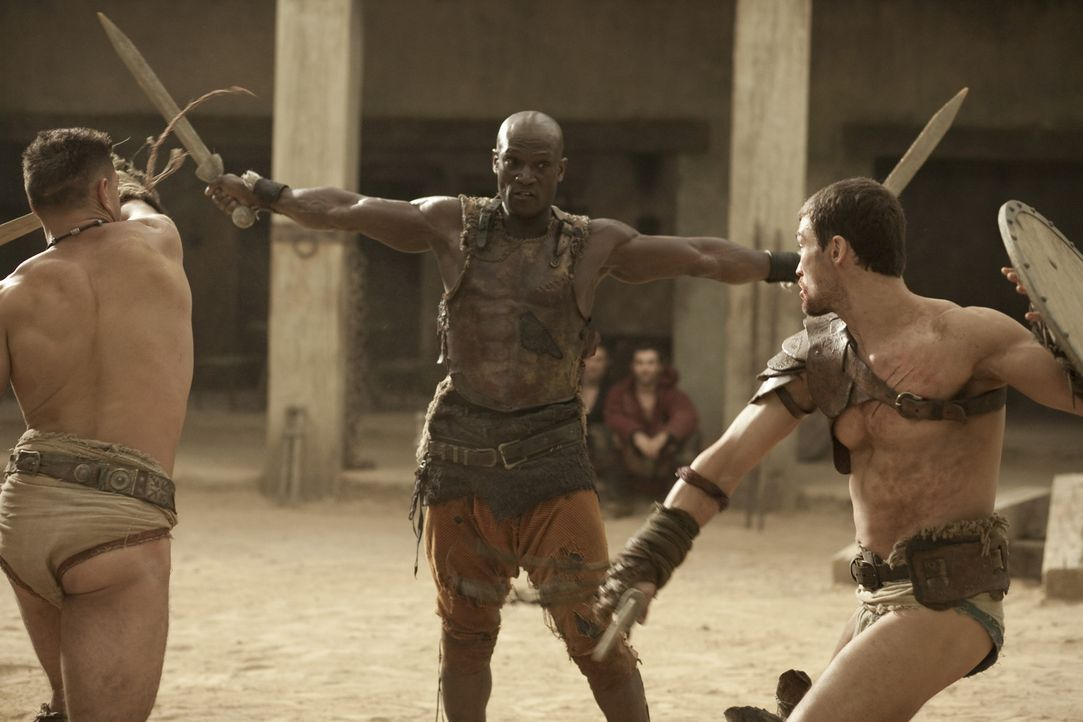 Drago (Peter Mensah, M.) ist der einzige Mann, der einen Kampf gegen Theokoles überlebt hat. Nun bereitet er Spartacus (Andy Whitfield, r.) und Cri... - Bildquelle: 2010 Starz Entertainment, LLC