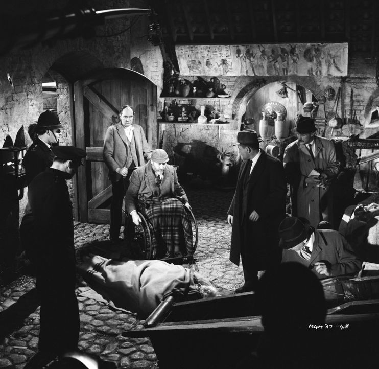 Da purzelt die Leiche aus dem Sarkophag: Inspektor Craddock (Charles 'Bud' Tingwell, hinten 2.v.r.) und Sergeant Bacon (Gordon Harris, hinten r.) en... - Bildquelle: Warner Brothers