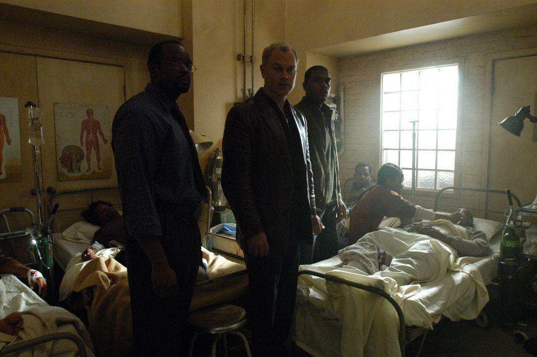 Connor (Neal McDonough, vorne M.) und Powell (Troy Winbush, vorne r.) sind fassungslos, als Dr. Onyiuke (Yvans Jourdain, vorne l.) ihnen das notdür... - Bildquelle: CBS Television
