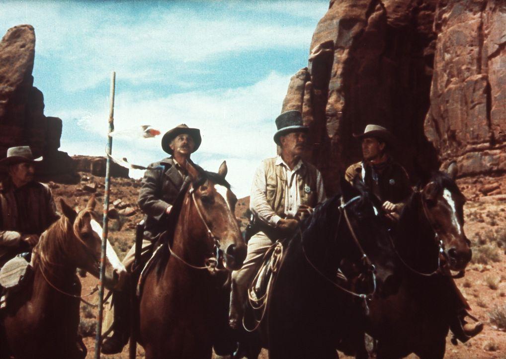Widerwillig ordnet sich Ethan (John Wayne, r.) Captain Sam Clayton (Ward Bond, 2.v.r.), der den Suchtrupp anführt, unter ... - Bildquelle: Warner Bros.