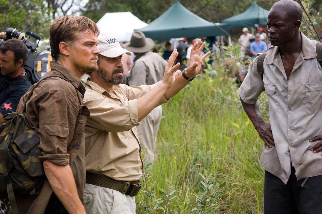 Regisseur Edward Zwick  (M.) gibt letzte Regieanweisungen an Leonardo DiCaprio (l.) und Djimon Hounsou (r.). - Bildquelle: Warner Bros.