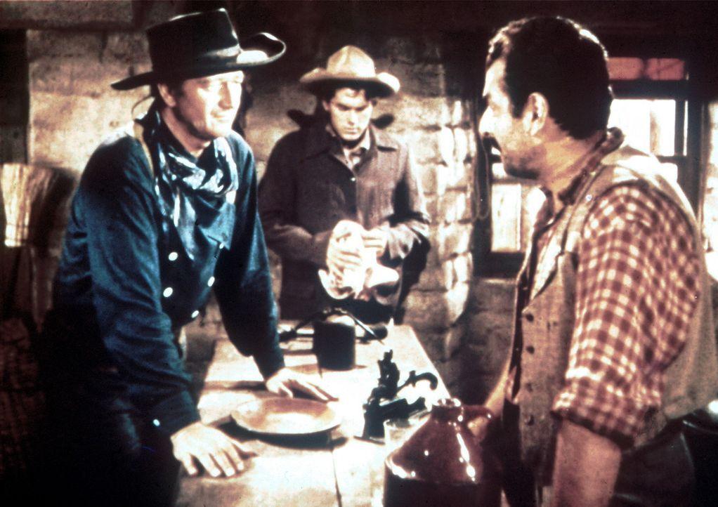 Ethan (John Wayne, l.) und Martin (Jeffrey Hunter, M.) erhalten vom Kaufmann Futterman (Peter Mamakos, r.) einen Hinweis auf Debbies Aufenthaltsort... - Bildquelle: Warner Bros.