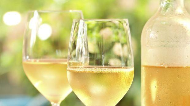 Gläser und Flasche mit gekühltem Weißwein